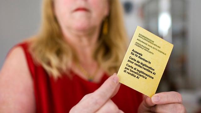 """Eine Frau mit rotem Kleid hält einen gelben Zettel, darauf steht """"Ausweis für IV Rente"""""""