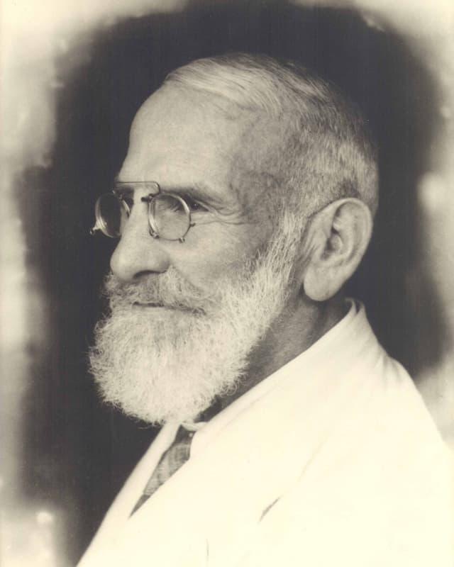 Schwarz-weiss Foto von Maximilian Bircher-Benner mit Bart und Brille im weissen Anzug.