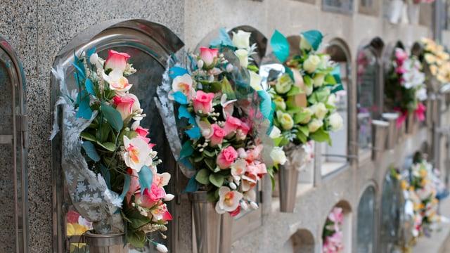 Eine mit bunten Blumen geschmückte Wand mit Urnengräbern