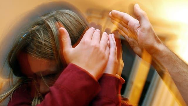 Ein Kind schützt seinen Kopf gegen eine schlagende Hand.