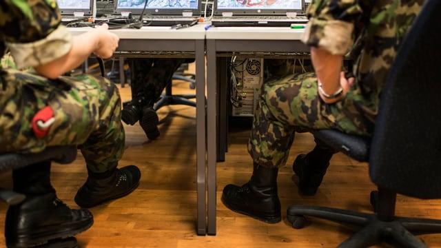 Soldaten sitzen an einem Tisch, auf dem mehrere Laptops stehen.