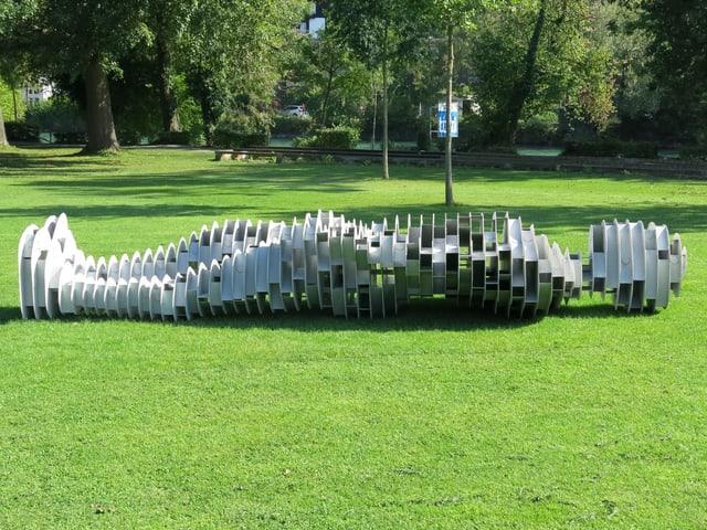 Eine Skulptur liegt auf der Wiese