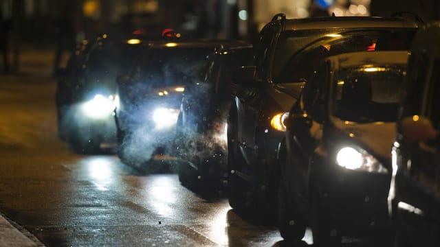 Sechs Autos stehen hintereinander auf einer Strasse. Es ist dunkel. Die Schweinwerfer leuchten.