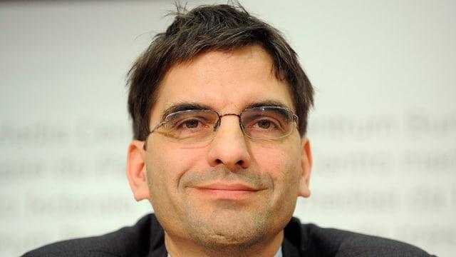 Aymo Brunetti lächelt anlässlich einer Konferenz in die Kamera.