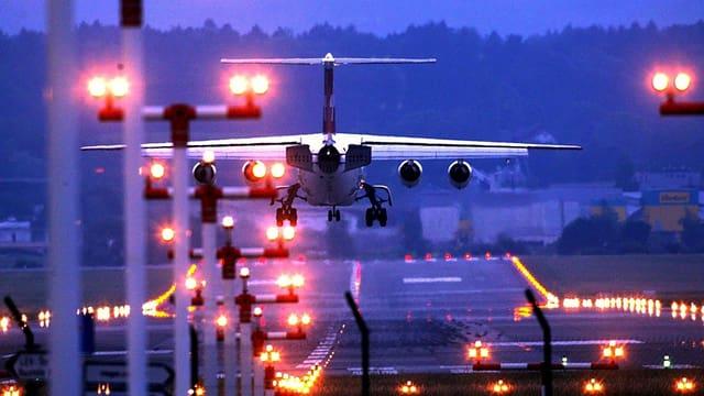 Flugzeug im Landeanflug in der Nacht, erleuchtete Pisten