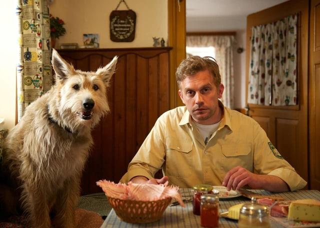 Ein Polizist sitzt am Tisch, auf dem Essen serviert ist. Neben ihm sitzt ein Hund.