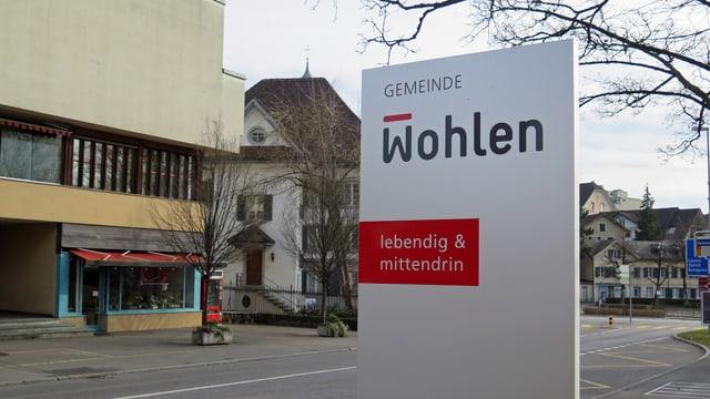 Schild vor dem Gemeindehaus, im Hintergrund Hauptstrasse und Dorf