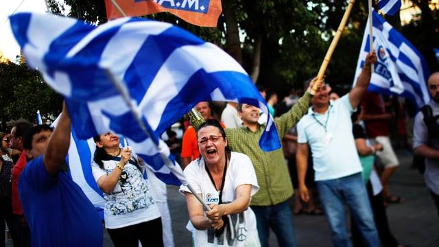 Menschen jubeln mit Griechenland-Fahnen.