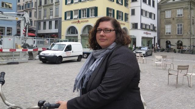 Eine Frau im Halbporträt steht mit ihrem Velo auf dem Münsterhof
