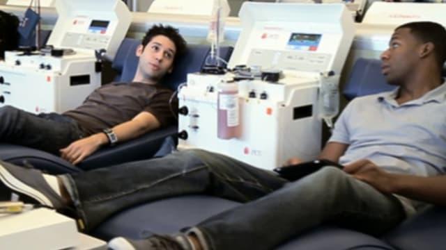 Zwei junge Männer, die Blutplasma spenden.