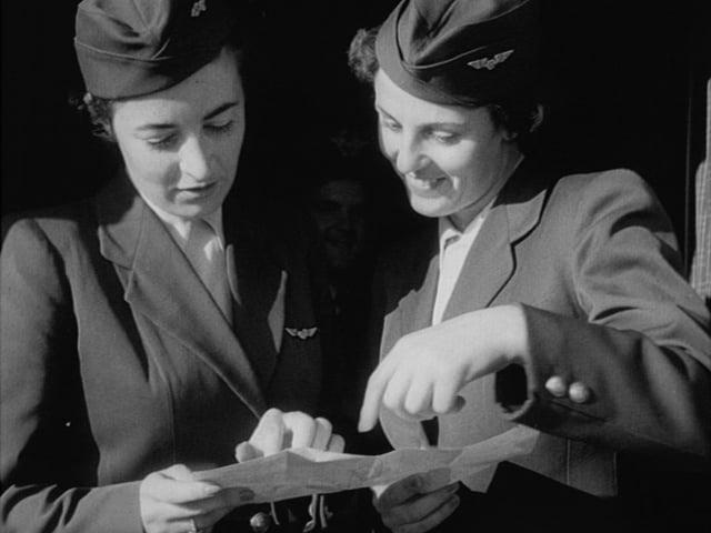 Zwei Stewardessen in altmodischen Uniformen studieren einen Faltplan.