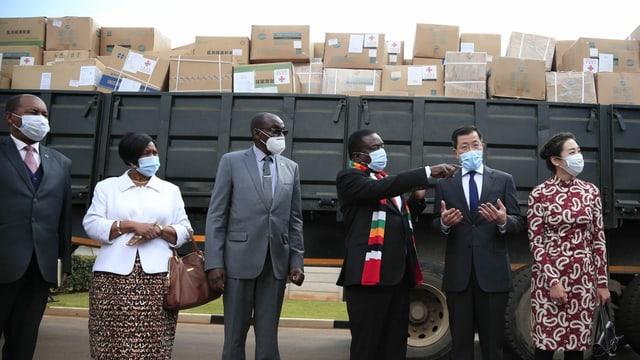 Chinesen und Afrikaner vor einem Wagen mit Hilfspaketen.