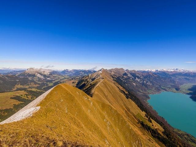 Ein schmaler Grat, links ein See, blauer Himmel.