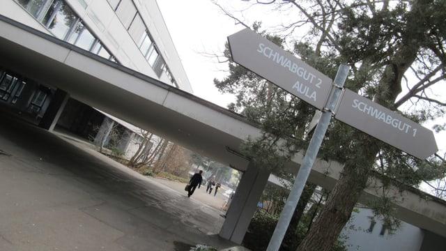 Ein Wegweiser vor den Schulgebäuden.
