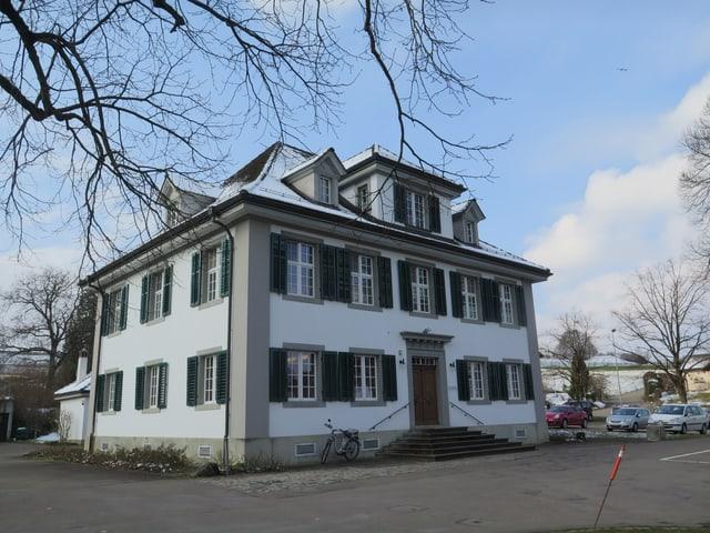 Ein herrschaftliches Haus mit grünen Fensterläden