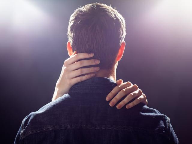 Die Rückansicht eines Mannes, um dessen Hals und Schultern zwei Frauenarme geschlungen sind.
