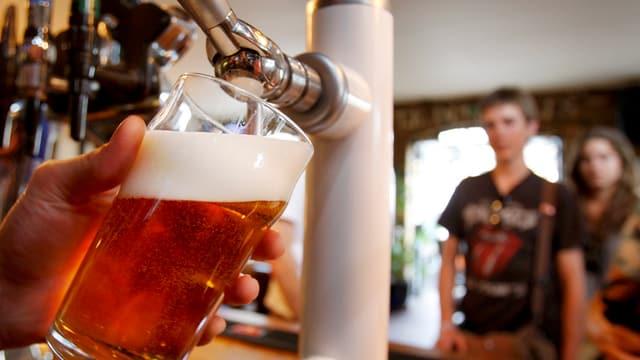 Ein Glas Bier, im Hintergrund ein Zapfhahn.