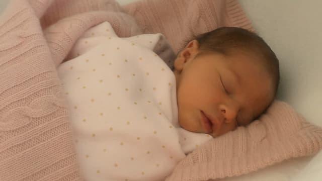 Ein Baby eingehüllt in eine rosa Wolldecke.