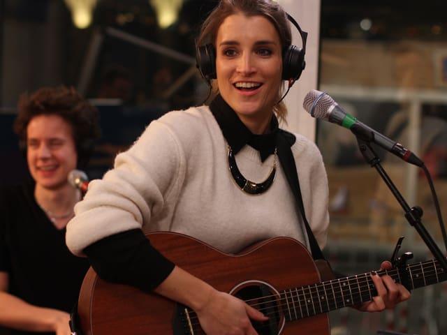 Sängerin Lina Button mit Gitarre in der Glasbox