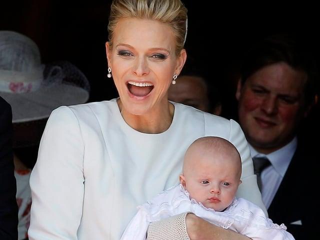 Charlène mit Baby im Arm und lachend.