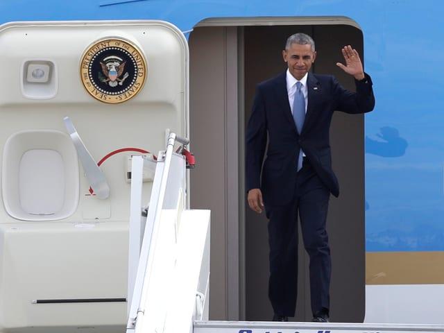 Barack Obama steigt winkend aus dem Flugzeug.