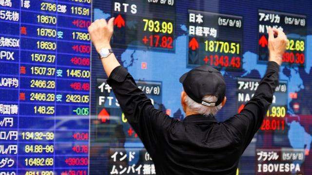 Ein Mann bejubelt die elektronische Börsenwand.