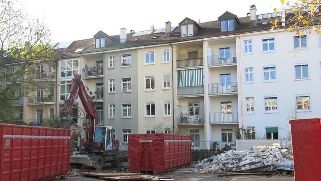 Blick in einen Basler Innenhof mit alten Liegenschaften. Im Vordergrund sieht man einen Baubagger.