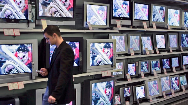Ein Mann schaut vor einer Wand von TV-Bildschirmen auf sein Handy.
