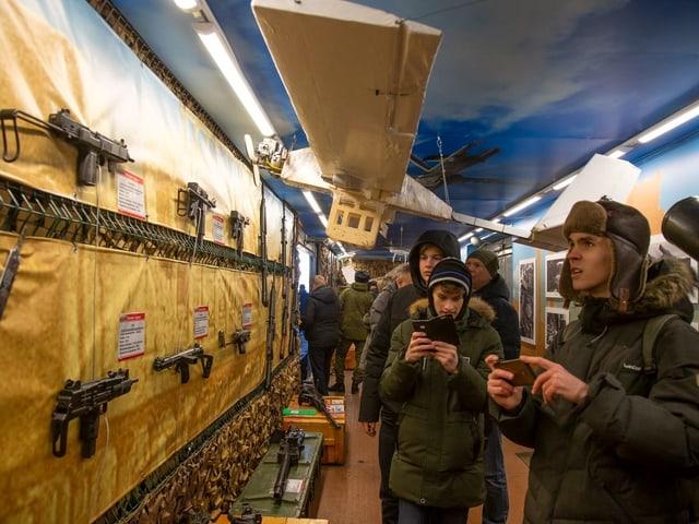 Besucher schauen im Zug auf präsentierte Gewehre.