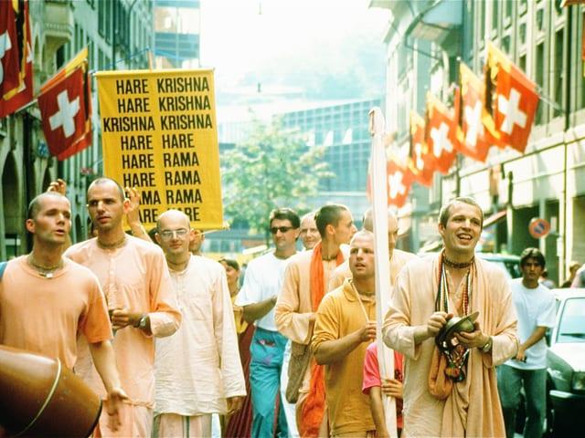 Junge Männer mit kurzgeschorenen Haaren und mandarinefarbigen Gewändern in einer Strasse, in der zahlreiche Schweizerfahnen hängen.
