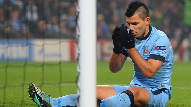 Sergio Agüero sitzt vor dem Torpfosten am Boden und hadert wegen einer verpassten Chance.