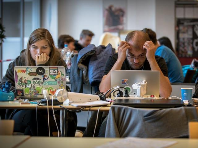 Ein Mann sitzt hinter einem Laptop und rauft sich die Haare.
