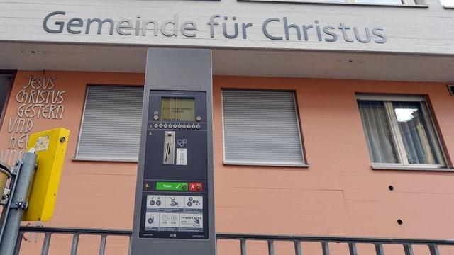 """Ein schmaler, grauer Automat steht vor einem Haus. Auf dem Haus prangt die Aufschrift: """"Gemeinde für Christus"""""""