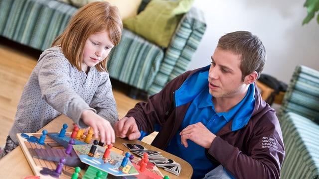 Ein Zivildienstleistender spielt mit einem Kind ein Brettspiel.