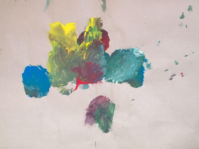 Auf Papier sind Farbkleckse in verschiedenen Farben zu sehen.