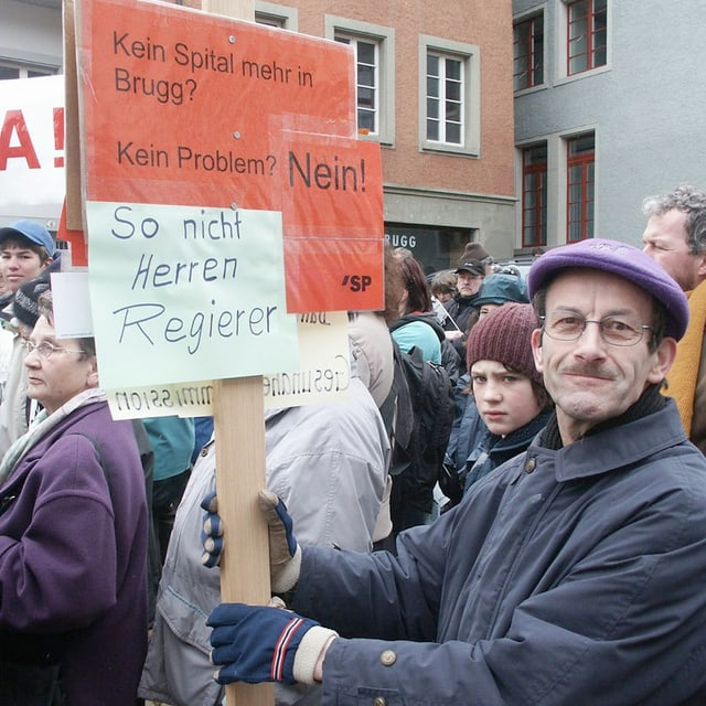 Mann an Demonstration hält ein rotes Schild in die Höhe