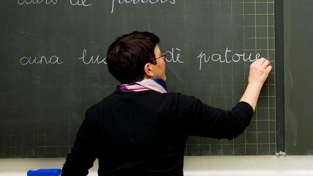 Eine Lehrerin schreibt an eine Wandtafel
