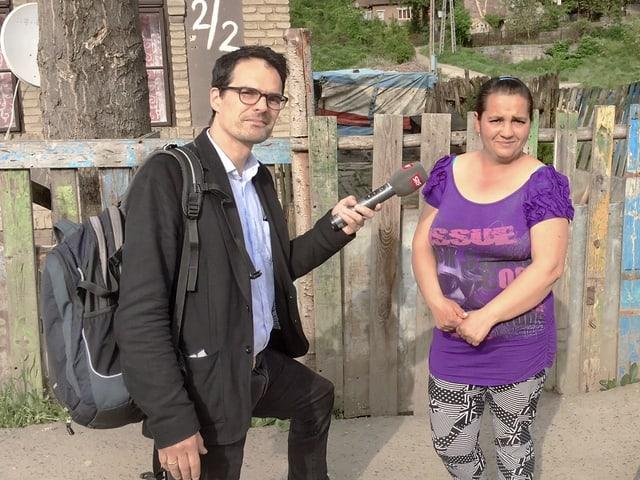 Korrespondent und Frau vor einem Zaun.