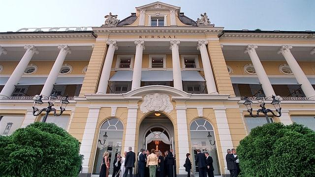 Casiono Luzern - gelbe-weisses Gebäude aus der Froschperspektive. Davor Menschen in Abendgarderobe.