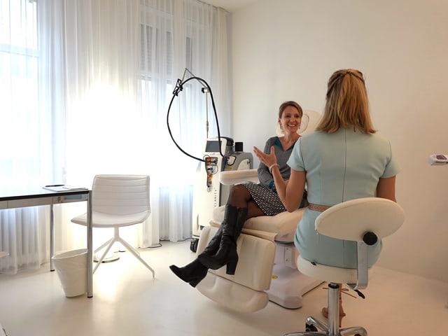 Frau sitzt auf Behandlungsstuhl und list im Gespräch mit Ärztin, die man von hinten sieht.