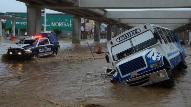 Eine überschwemmte Strasse und ein umgekippter Bus.