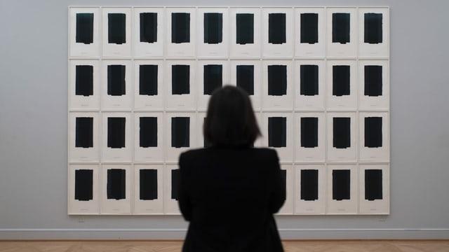 Eine Frau steht vor einer Wand mit lauter schwarzen Blättern.