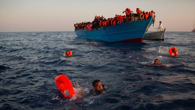 Ein überfüllte Flüchtlingsboot auf hoher See, Menschen mit orangen Rettungswesten springen ins und schwimmen im Wasser.