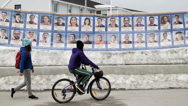 Zwei Personen gehen an Wahlplakaten vorbei