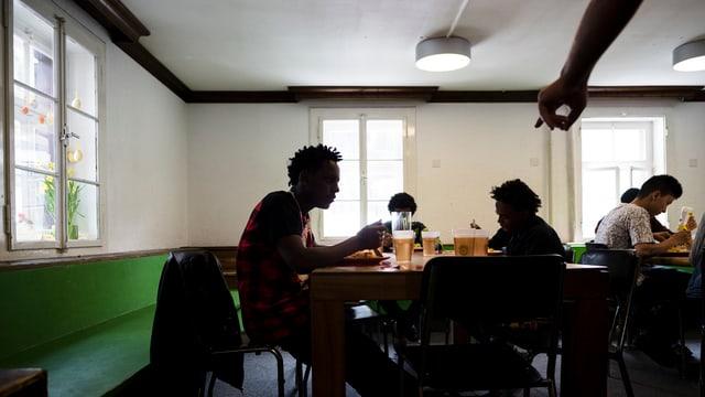 Junge Asylsuchende sitzen an Tischen