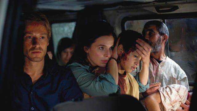 Zwei Männer, eine Frau und ein verletztes Kind sitzen in einem Bus.