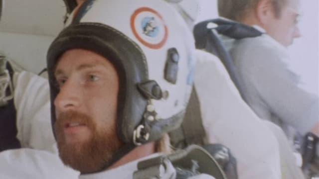 Kurt Schaad in Weltraumanzug in einem Flugzeug.