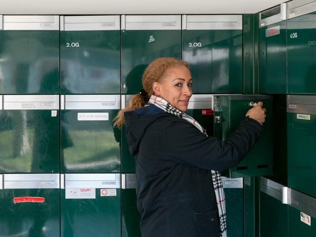 Eine Frau steht vor Briefkästen.