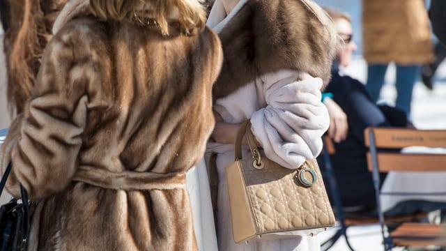 Zwei Damen tragen Pelzmäntel.