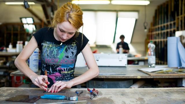 Eine junge Frau schneidet auf einer Werkbank Glas.